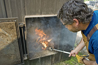 Picture of a man stoking a smoldering fire in an Outdoor Wood Boiler.